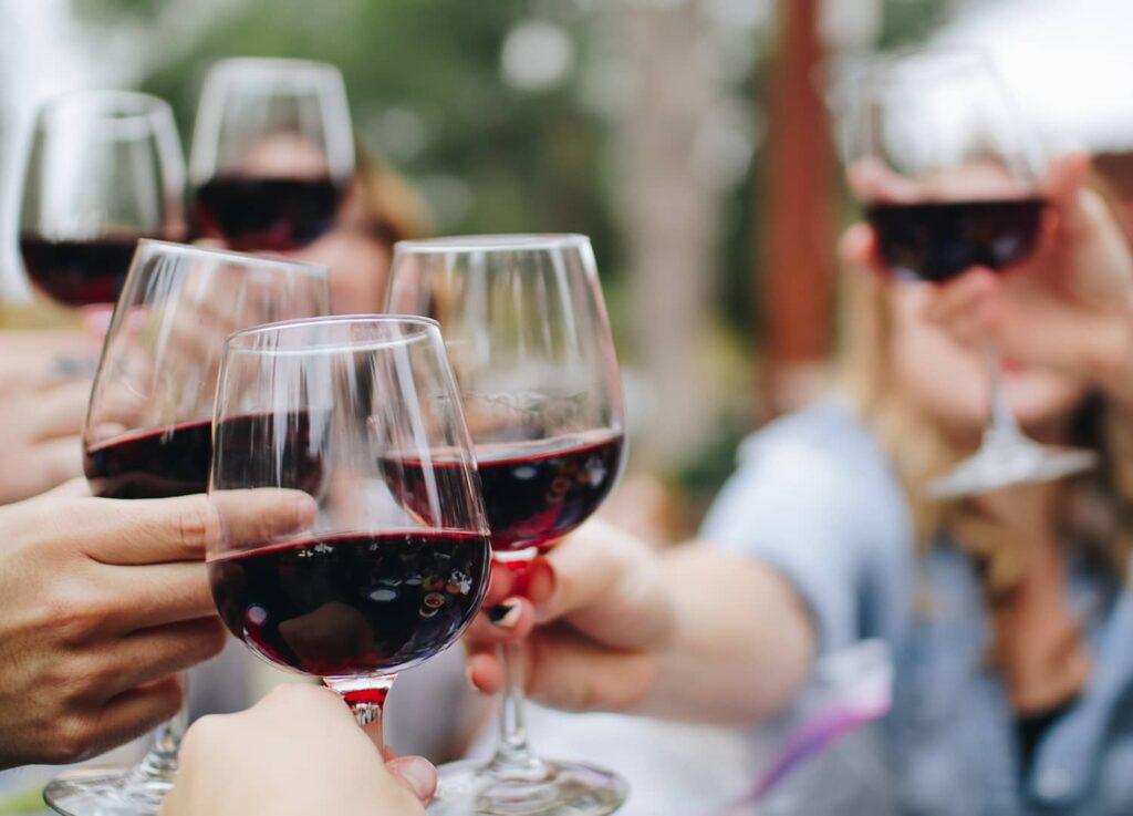Seks personer hæver vinglas med vin fra Winedrop til en skål